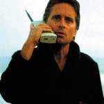 Here is Michael Douglas in Wall Street!  The telephone is almost as big as a football! http://trendycellular.com/blog/old-school-fridays-first-cell-phone-in-a-movie/