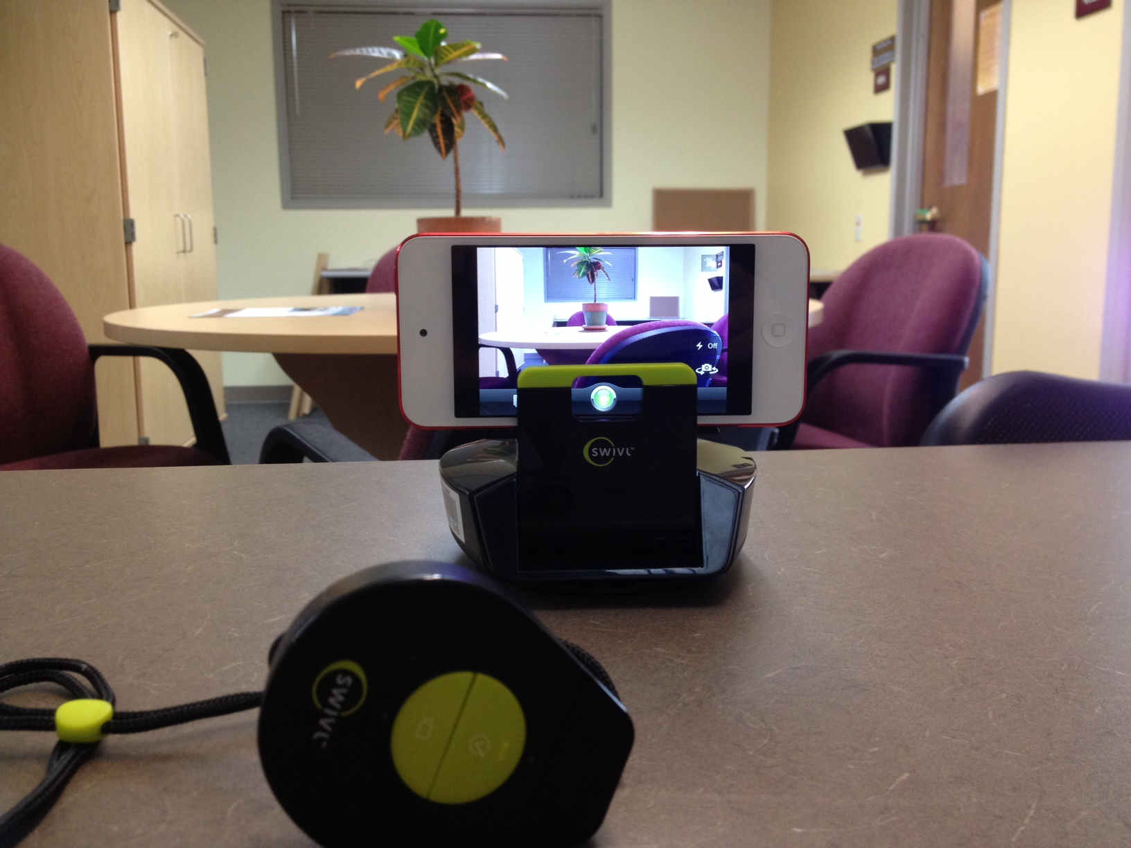 Swivl with iPod 5th generation. Remote (foreground) is worn by the presenter and has a built in microphone that integrates with your iDevice when the Swivl app is installed and the iDevice is plugged into the Swivl base. NOTE: Not compatible with all iDevices (see Media Services for details).