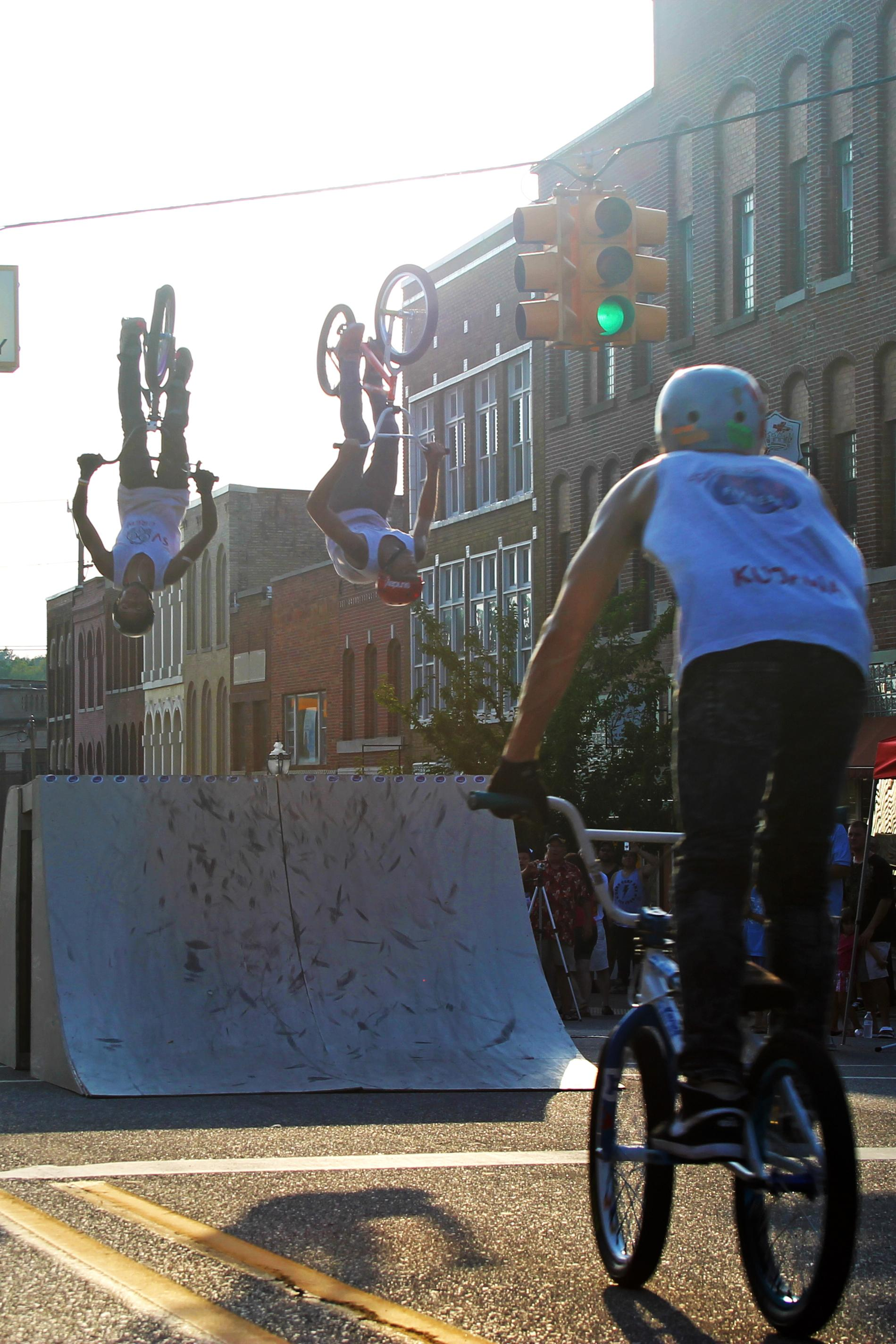 BMX bikers doing a flip off of a ramp