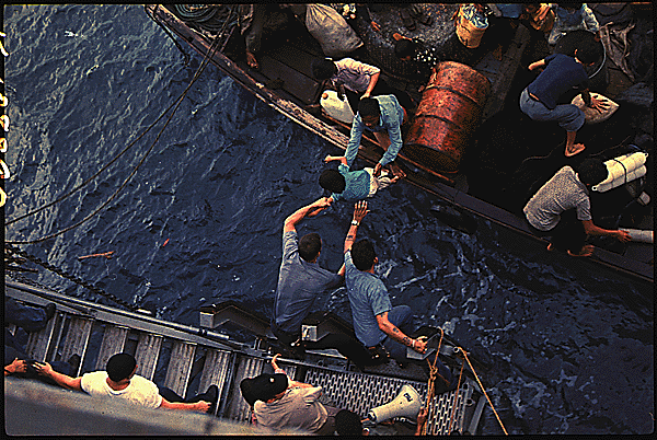 Crewmen of the Amphibious Cargo Ship USS Durham Take Vietnamese Refugees Aboard a Small Craft, 1975, via New Old Stock (Copyright Free).